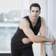Man in athletic gear leaning on ballet bar - Stock Photo