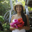 South American woman carrying bouquet of flowers — Stock Photo