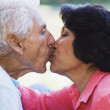 Senior Hispanic couple kissing - Stock Photo
