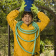 Boy holding potted plant on head and hose on shoulders - Stock Photo