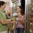 Hispanic couple looking at flowers in florist shop - Stock Photo