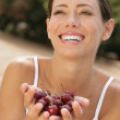 Foto Stock: Young woman smiling with hands full of cherries