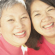 Close up of senior Asian mother and grown daughter smiling — Stock Photo