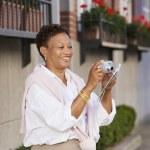 Mature woman taking photograph — Stock Photo
