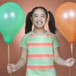 Young girl holding balloons — Stock Photo #13238540
