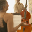 Senior African couple singing and playing upright bass - Stock Photo
