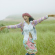 Woman laughing with arms outstretched in field - Stock Photo