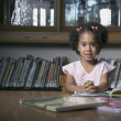 Stock Photo: Portrait of girl reading book in library