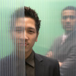 Businessmen obscured by glass walls - Stock Photo