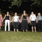 Hispanic women holding hands in a row — Stock Photo