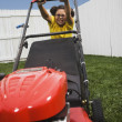 Mixed Race girl pushing lawn mower — Stock fotografie