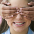 Close up of girl with hands over another girls eyes - Stock Photo
