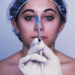 Native Americwomlooking at syringe — Stockfoto #13238664