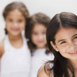 Hispanic girl smiling with sisters in background — Stock Photo
