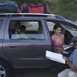 Stock Photo: Man examining map by his family minivan