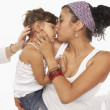 Young woman kissing her daughter — Foto Stock