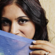 Portrait of woman holding scarf over mouth - Foto Stock