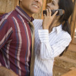 Hispanic couple talking on cell phone in construction site - Stock Photo
