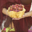 Stock Photo: Young woman holding a bowl of grapes