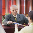 Businessman receiving brochure from a receptionist — Stock Photo