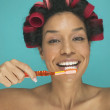 Royalty-Free Stock Photo: Portrait of woman with rollers in hair brushing teeth