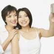 Studio shot of Asian mother and adult daughter talking self portrait — Stock Photo