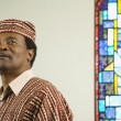 Middle-aged African man next to stained glass window — Stock Photo