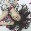Asian woman laying on floor with rose petals — Stock Photo