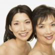 Stock Photo: Studio shot of Asian mother and adult daughter smiling