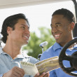 Two men smiling at each other in golf cart — Stock Photo #13238788