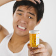 Frustrated Asian man holding medication bottle — Stock Photo