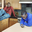 Stock Photo: Brothers talking on cell phones in kitchen