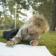 Young girl drawing outside — Stock Photo #13238846