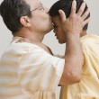 Stock Photo: Father kissing son's forehead