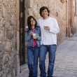Hispanic couple with coffee on sidewalk - Stock Photo