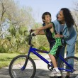 Hispanic mother smiling at son on bicycle — Stock Photo