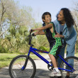 Hispanic mother smiling at son on bicycle — Stock Photo #13238865