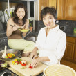 Asian mother and adult daughter in the kitchen with food — Stock Photo