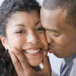 Stock Photo: AfricAmericmkissing girlfriend on cheek