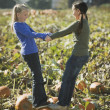Two girls standing on pumpkin in pumpkin patch — Stock Photo #13238890