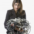 Businesswoman holding tangled computer cords — Stock Photo