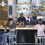 Двое молодых людей, сидя в баре глядя на молодую женщину — Стоковое фото