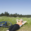 Woman laying in grass next to bicycle — Stock Photo