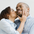 African woman kissing husband on cheek — Stock Photo