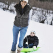 Asian women pulling child on sled — Stock Photo