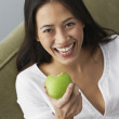 Asian woman eating apple — Stock fotografie