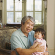 Stock Photo: Asigrandfather holding young granddaughter on lap