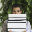 Man holding stack of notebooks — Stock Photo
