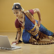 Stock Photo: Indian woman in traditional dress using a laptop