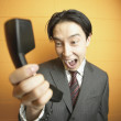 Businessman shouting at phone — Stock Photo